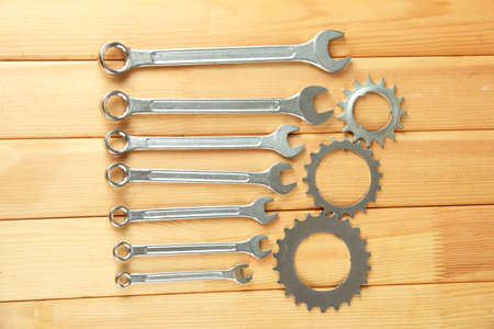 Metal cogwheels and spanners on wooden background Stock Photo - 16772619