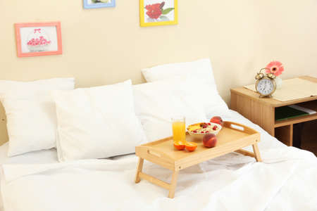 wooden tray with light breakfast on bed photo