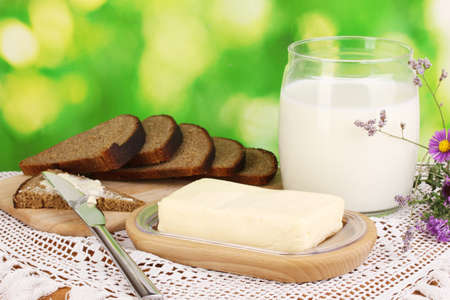 Butter on wooden holder surrounded by bread and milk on natural background Stock Photo - 16830593