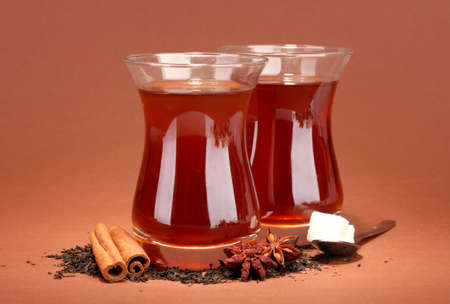 glasses of Turkish tea, on brown background photo
