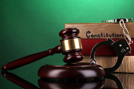 Gavel, handcuffs and books on law on green background Stock Photo - 16830605