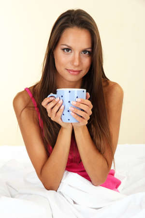 young beautiful woman with cup in bed Stock Photo - 17051902
