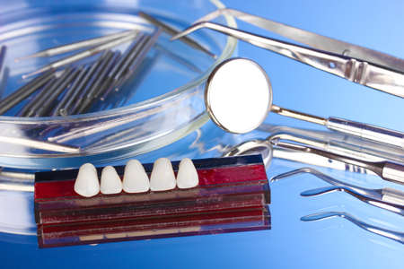 Set of dental tools with denture on blue background photo