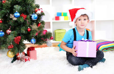 Child in Santa hat sits near Christmas tree with gift in hands Stock Photo - 17282593