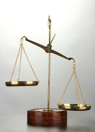 balance scale: Escamas de oro de la justicia sobre fondo gris