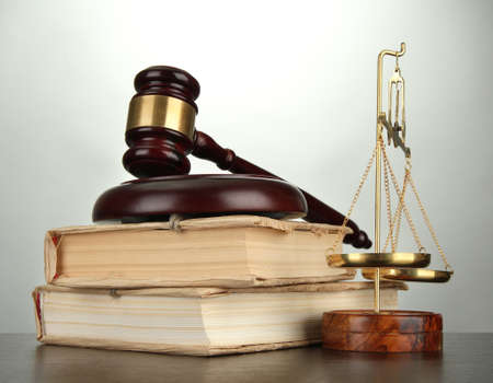 business law: Golden scales of justice, gavel and books on grey background Stock Photo