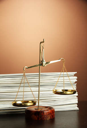 Gold scales of justice and folders on brown background photo