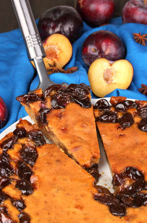Tasty pie on plate with plums on wooden table Stock Photo - 16830730