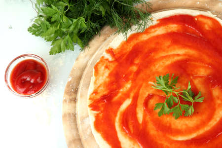 Pizza dough with tomato sauce on wooden board isolated on white photo
