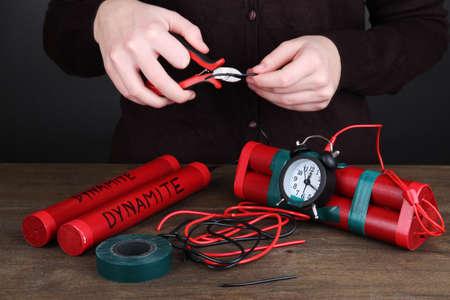 detonating: Human makes timebomb on wooden table on black background