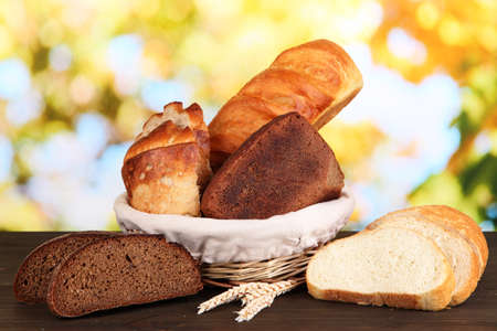Fresh bread in basket on wooden table on natural background Stock Photo - 16830742