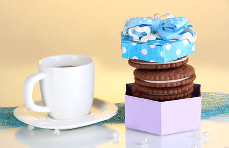 Chocolate cookies with creamy layer and cup of coffe on yellow background Stock Photo - 16830484