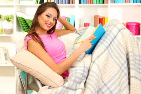 Portrait of female reading book while lying on couch Stock Photo - 17281834