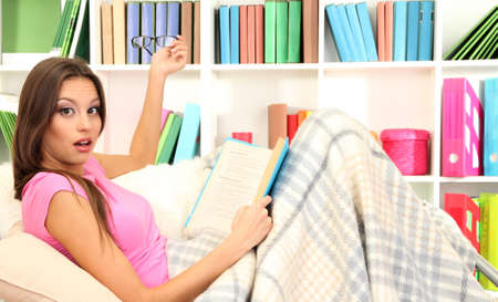 Portrait of female reading book while lying on couch Stock Photo - 17281830