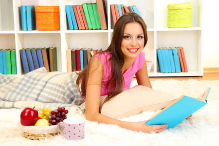 Young female relaxing on floor at home reading book Stock Photo - 17281831