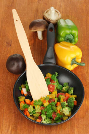 Sliced fresh vegetables in pan with spices and ingredients on wooden table Stock Photo - 16830735