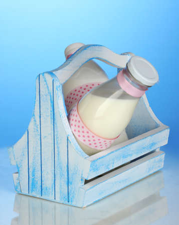 Milk in bottles in wooden box on blue background photo