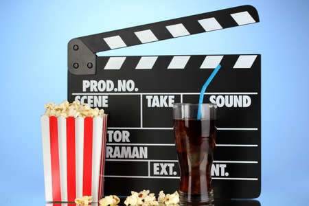 Movie clapperboard, cola and popcorn on blue background Stock Photo - 16859435