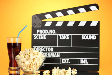 Movie clapperboard, cola and popcorn on orange background Stock Photo - 16859447