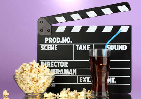 Movie clapperboard, cola and popcorn on purple background Stock Photo - 16859479