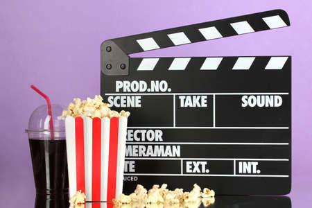 Movie clapperboard, cola and popcorn on purple background Stock Photo - 16859467