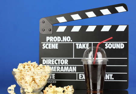 Movie clapperboard, cola and popcorn on blue background Stock Photo - 16859472