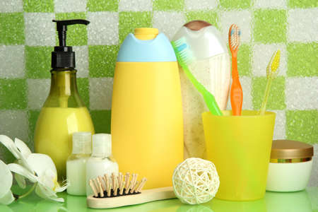 Bath accessories on shelf in bathroom on green tile wall background photo