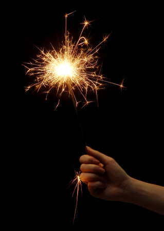 sparklet: beautiful sparkler in woman hand on black background  Stock Photo
