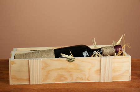 Wine bottle in wooden box on wooden table on brown background Stock Photo - 16859539
