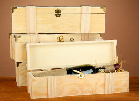 Wine bottle in wooden box on wooden table on brown background Stock Photo - 16859468