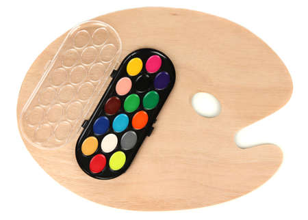 Wooden art palette with paints isolated on white photo