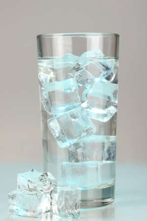 Ice cubes in glass on light blue background Stock Photo - 16859485