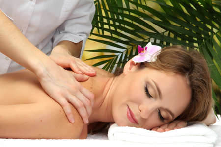 beautiful woman in spa salon  getting massage, on palm leaves background photo