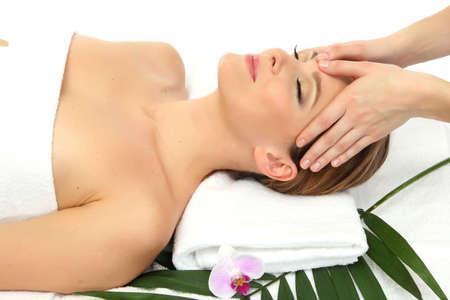 Portrait of beautiful woman in spa salon taking head massage photo