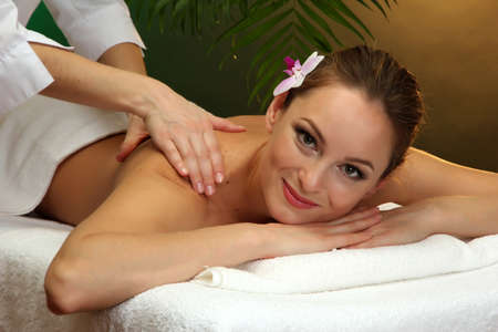 beautiful young woman in spa salon getting massage, on green background Stock Photo - 17282444