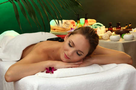 beautiful young woman in spa salon with spa stones, on green background photo