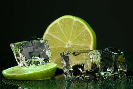darck: Ice cubes with lime on darck green background Stock Photo