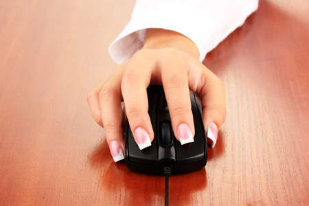 office equipment: womans hands pushing keys of pc mouse, on wooden table close-up
