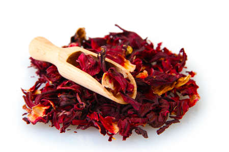 sepals: aromatic Hibiscus tea with wooden shovel, isolated on white