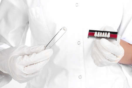 A dentists hands with denture and dental tweezers photo