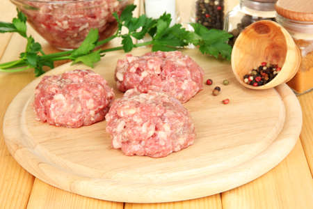 Raw meatballs with spices on wooden table photo