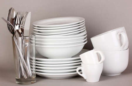 Clean white dishes on grey background photo