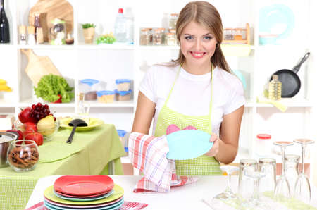 A young girl dries dishes in kitchen photo