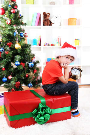 Little boy with big gift and clock in anticipation of New Year photo