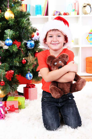 Little boy in Santa hat sits near Christmas tree with gift in hands photo