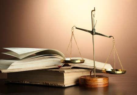 balanza de justicia: Escamas de oro de la justicia y libros sobre fondo marrón Foto de archivo