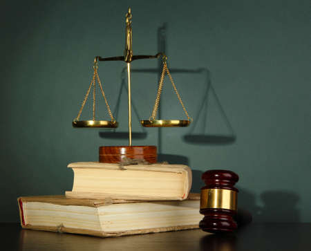 Golden scales of justice, gavel and books on grey background photo