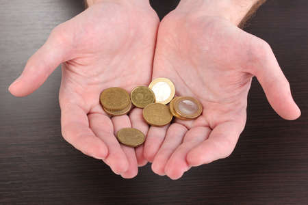 economise: Counting money in hand on wooden table background