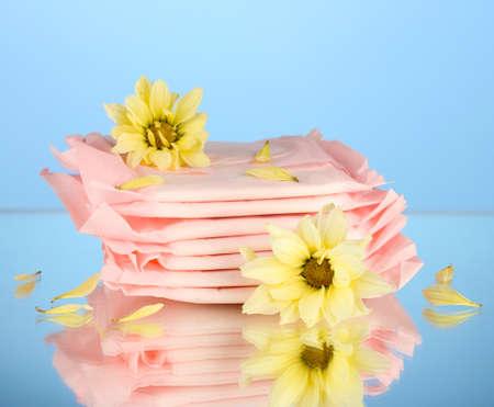 breathable: Salvaslip in confezione singola e fiori gialli su sfondo blu, close-up Archivio Fotografico