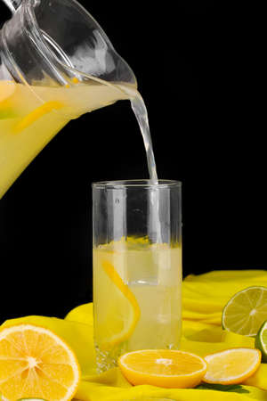 Citrus lemonade in glass and pitcher of citrus around on yellow fabric on wooden table close-up Stock Photo - 16895144